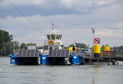 Sie ist für bis zu sechs Autos, 28 Fahrräder und 70 Personen ausgelegt.] An einem zwischen zwei Masten (Pylonen) hoch über den Rhein gespannten Sicherungsseil gleitet die Fähre im Normalbetrieb nur per Ruderstellung durch Strömungskraft und ohne eigenen Antrieb über den Strom. Aus Sicherheitsgründen ist die Fähre zusätzlich mit einem Motorantrieb ausgestattet.